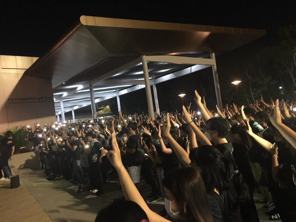 A picture of the demonstration at Mae Fah Luang University showing the protestors doing the three-finger salute