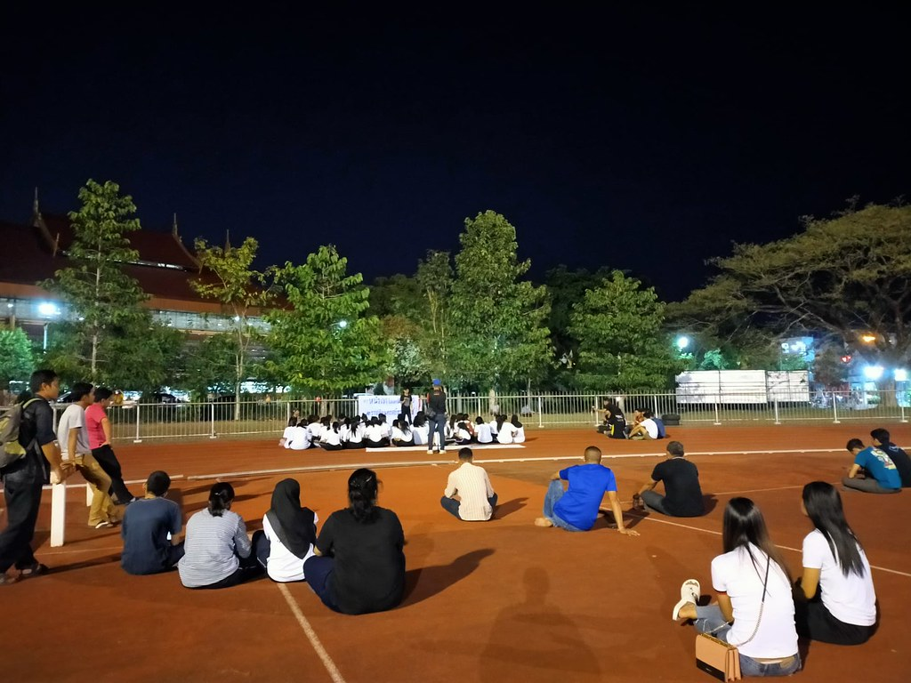 A picture of the demonstration at the Nakhon Si Thammarat Rajabhat University showing around 20 protestors sitting on the ground, surrounded by plainclothes officers and members of the public.