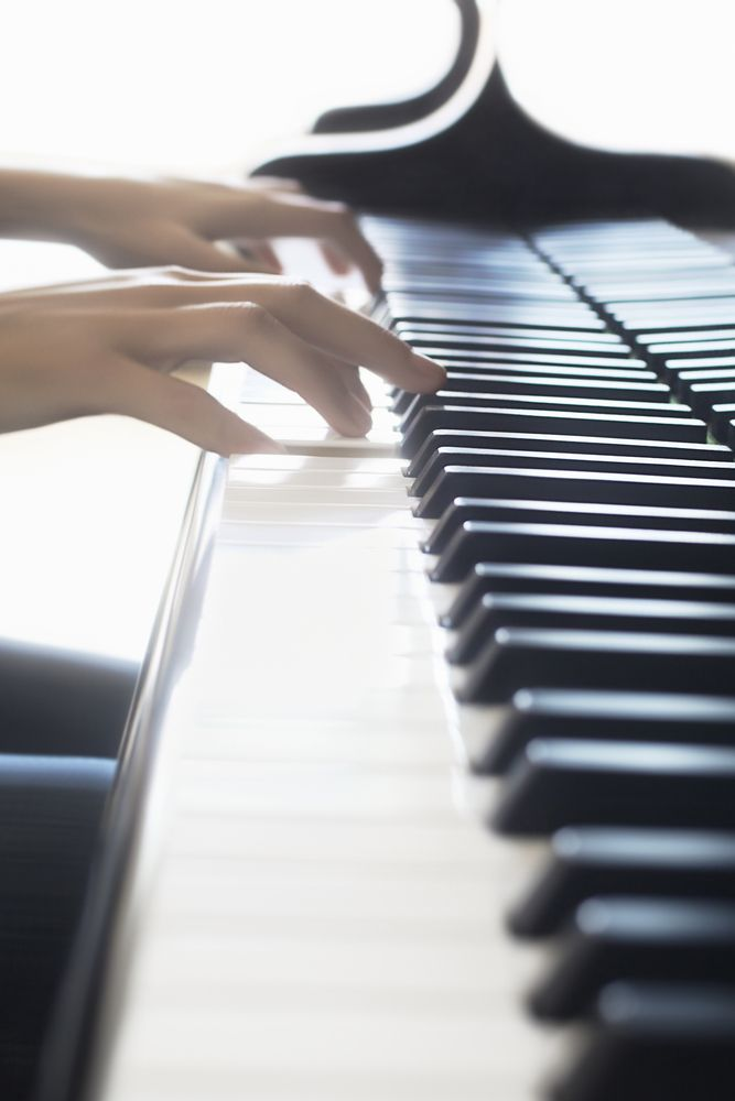 closeup of two hands playing a piano keyboard