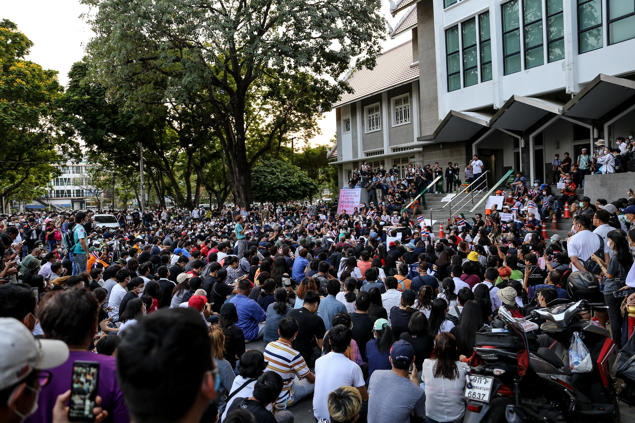 A wide shot of the demonstration at Kasetsart University early in the evening, showing a large group of participants gathering in front of the university auditorium.