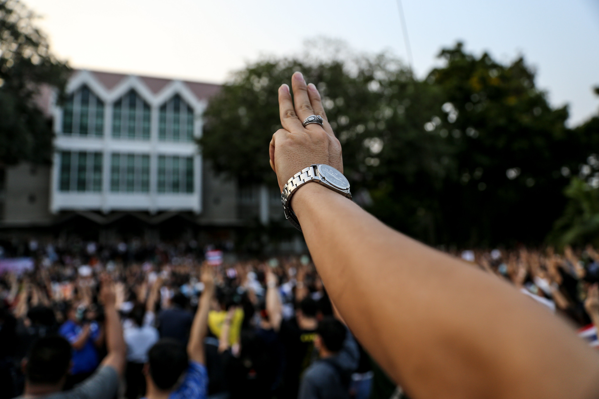 A picture of the demonstration at Kasetsart University. In the foreground is the hand of a protestor doing the three-finger salute. The crowd is seen in the background with many also doing the three-finger salute.
