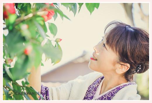椿の花を眺める着物姿の女性