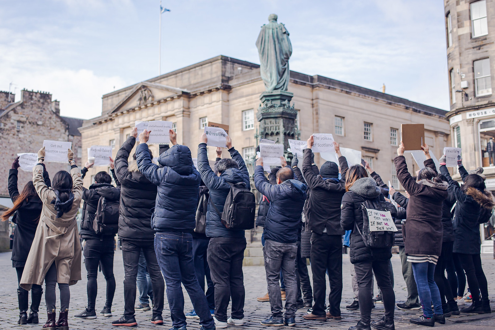 Thai students in Scotland protesting in Edinburgh, all wearing dark jackets and holding protest signs above their head.