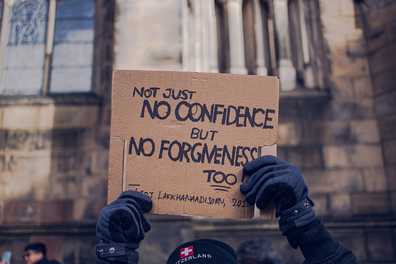 "A protest sign written on cardboard with the message ""Not just no confidence but no forgiveness too"" being held by a pair of hands wearing dark gloves."