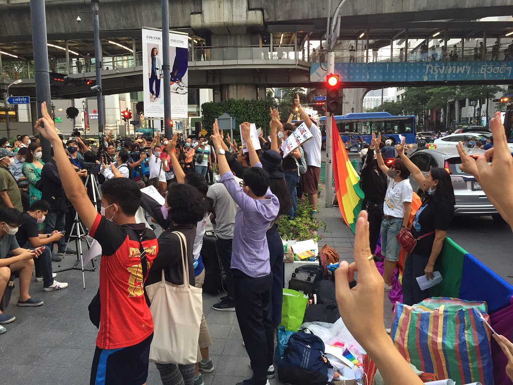 Protestors standing at the Ratchaprasong Intersection doing the three-finger salute with the LGBT rainbow flag behind them.