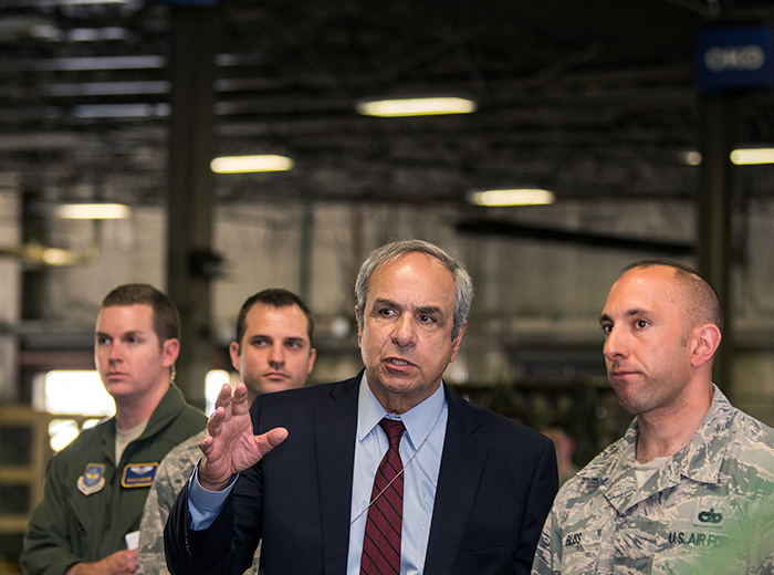 Four men stand inside a building at an Air Force base.
