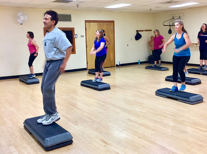 A group of people taking an exercise class at the YMCA.