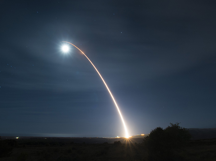 A launched missle creates an arc of light in the night sky.