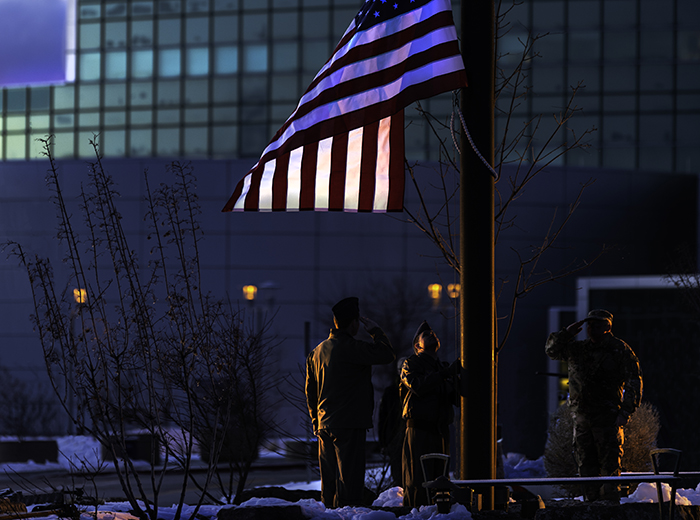 Two men salute as a third man raises an American flag on a flagpole outside of the Lab's NSSB.