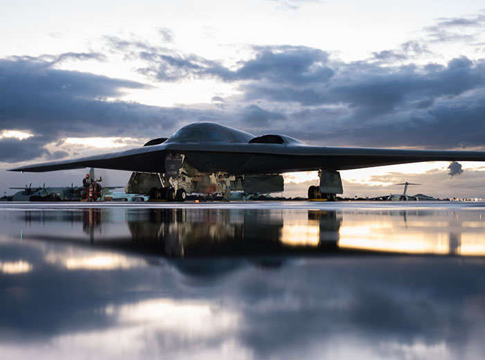 A B-2 Spirit aircraft sitting on the tarmac. The morning sky reflects off of the tarmac in front of the aircraft.