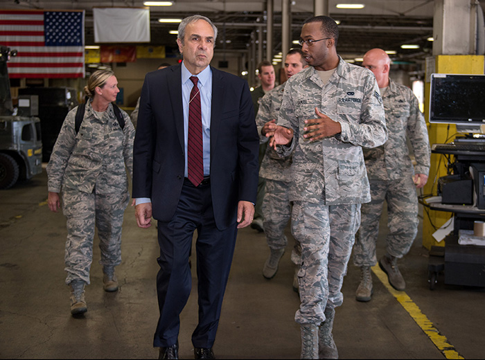 A man walks with a group of uniformed Air Force individuals.