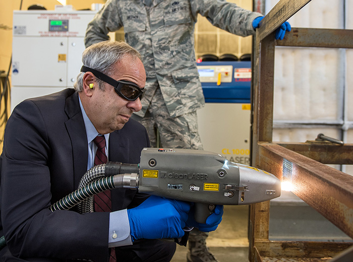 A man wearing safety goggles uses a handheld laser while another man stands behind him and watches.