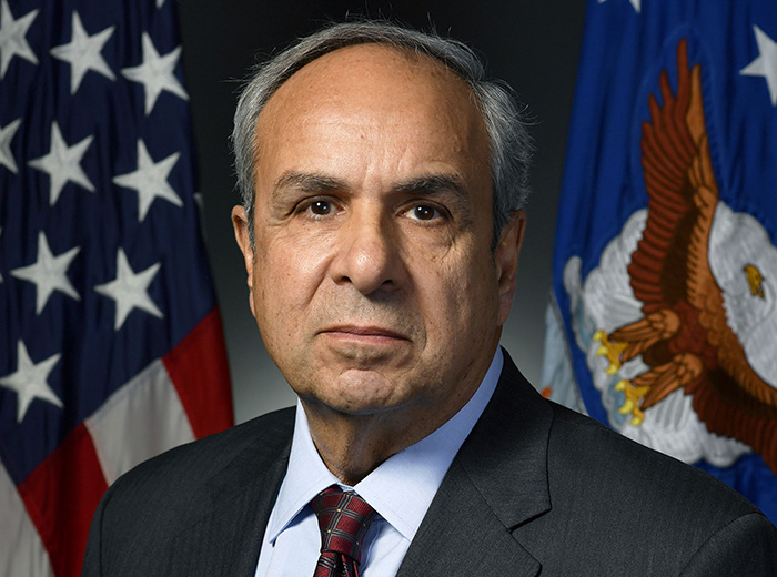 Portrait of a man standing in front of two flags.