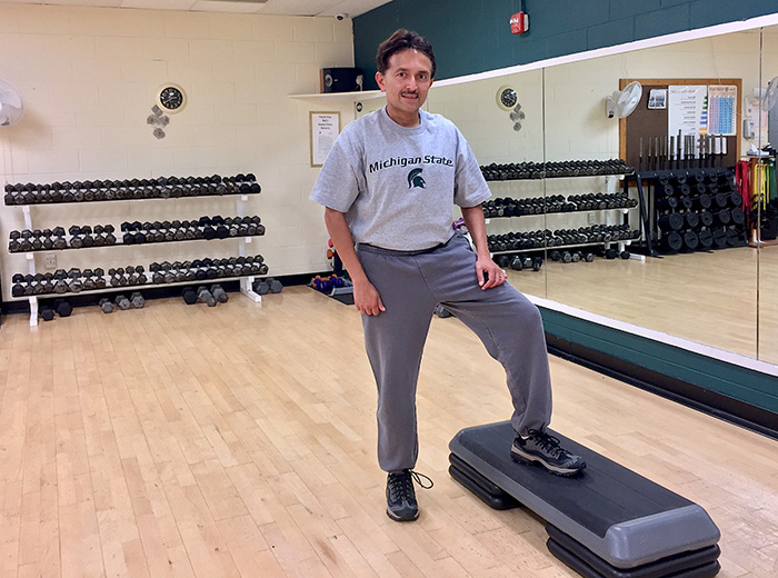 A man puts his foot on an exercise step at the YMCA.