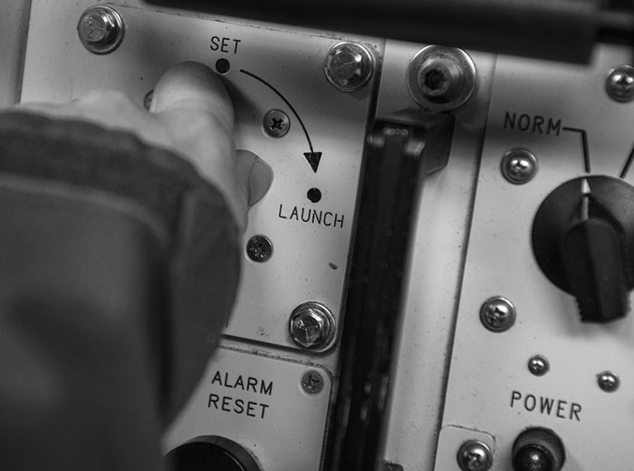 A hand preparing to turn a knob from the set position to the launch position.