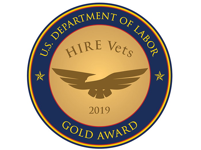 An illustration of the gold award, which is circular with a flying eagle silhouette in the center. The award has the words U.S. Department of Labor Gold Award outside of the eagle and the words HIRE vets and 2019 above and below the eagle, respectively.