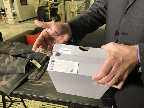 An RFID tag is held next to a shoebox.