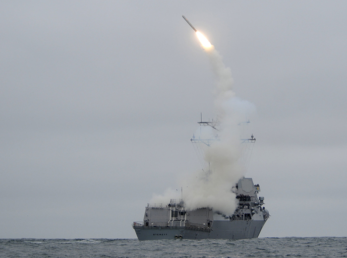 A missile launched from a ship begins to make an arc in the sky.