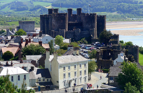 Conwy Castle with its towers and turrets from a hill, with the village in front