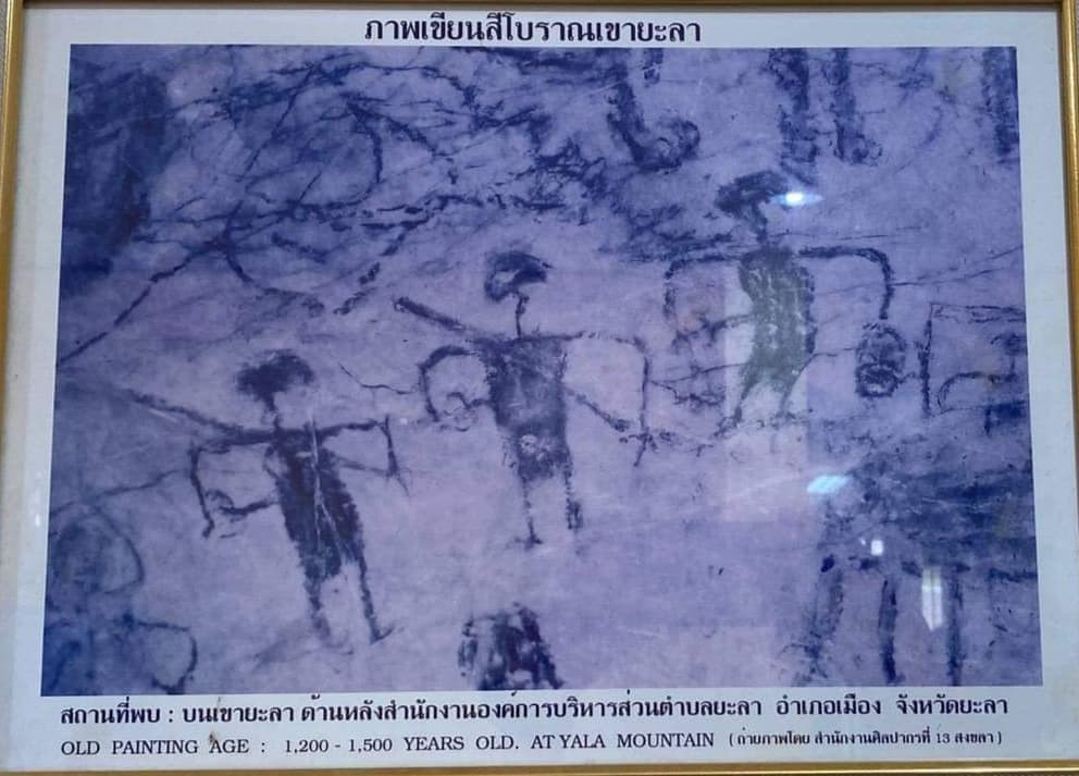 A picture of a cave painting in a frame. The text at the bottom reads: old painting age: 1200 - 1500 years old at Yala Mountain.