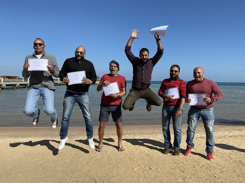 A group of Green Fins assessors jumping in celebration and holding their certificates after becoming qualified. They are standing in front of the ocean with bright blue skies in the background.