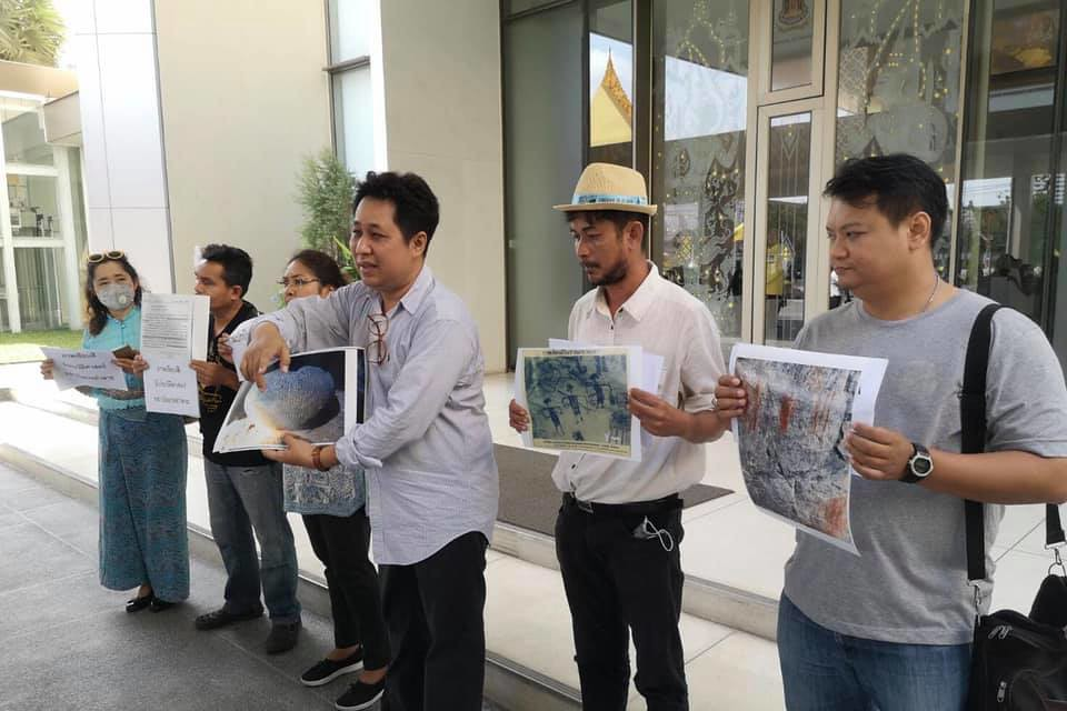 A picture of a group of five people holding pictures of cave paintings printed on paper in front of the Ministry of Culture building.