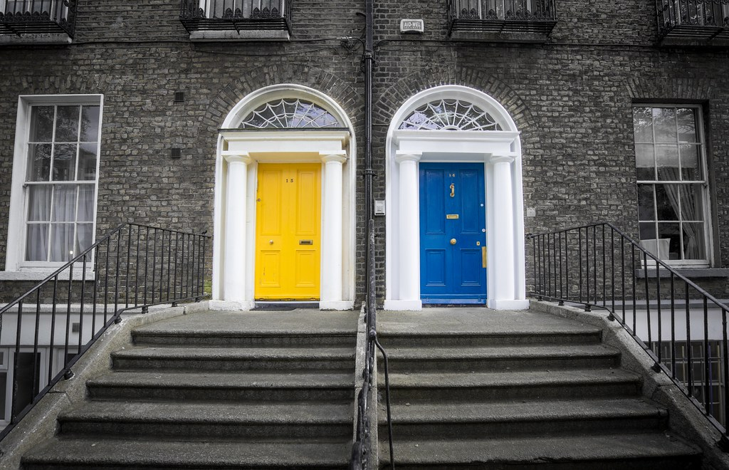 The front doors of two hours - one is blue and one is yellow