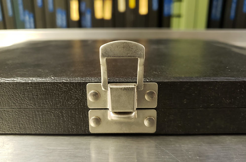 newer slide box laying flat on a table; the latch is lifted upwards and the box appears to be rightside up