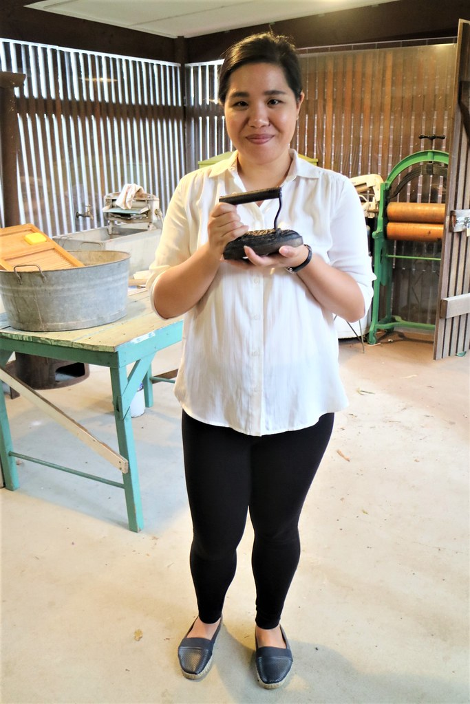 Volunteer in the laundry, holding a flat iron, Heritage Village, Fairfield City Museum and Gallery, Smithfield, NSW