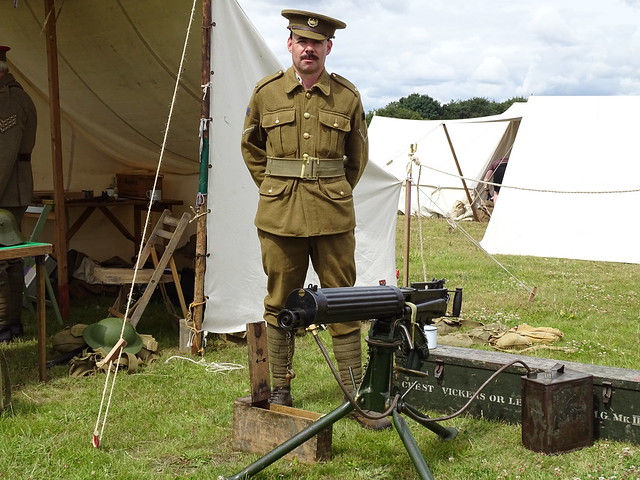 FIRST WORLD WAR SOLDIER STANDING NEXT TO A MACHINE GUN WEARING BRITISH ARMY UNIFORM AT DANYMS HALLL AERODROME CAR AND MILITARY SHOW IN AN EAST LONDON BOROUGH SUBURB ENGLAND  DSC03000