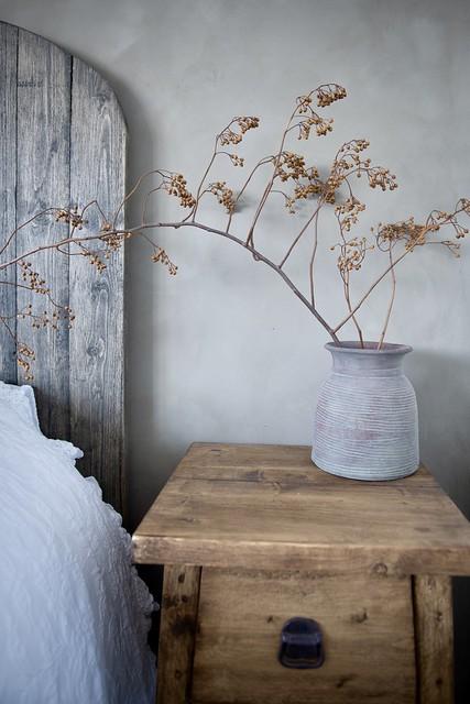 Grijze vaas met rozenbottel tak op nachtkastje