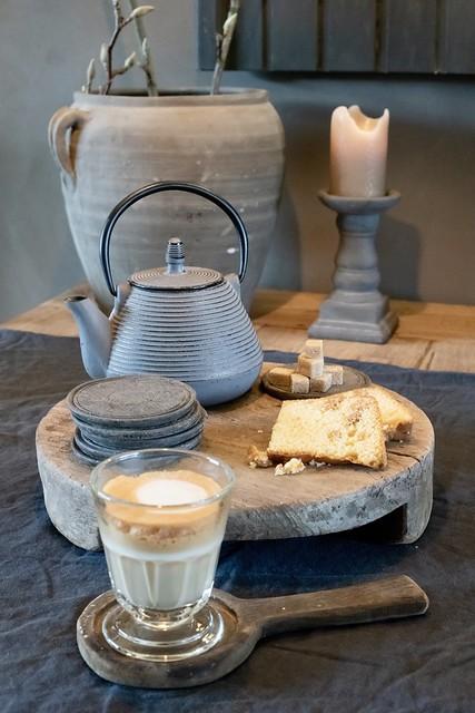 Houten plank grijze theepot koffieglas met onderzetter
