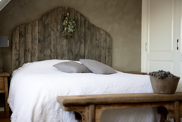 Kalkverf muur houten hoofdbord bed landelijke slaapkamer