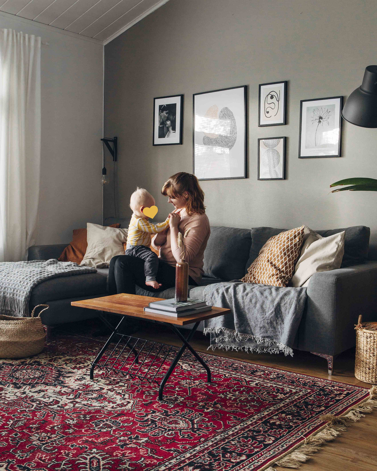 Pinossa-blogin kirjoittaja istuu olohuoneessa harmaalla sohvalla lapsi sylissään.