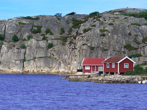 Rocky coastline with red buildings at Gronemad is a small town along the Bohuslän Coast of Sweden