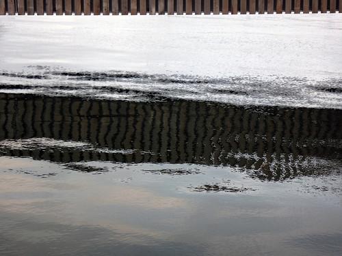 Striped reflections of a bridge in rippled water in Aarhus, Denmark