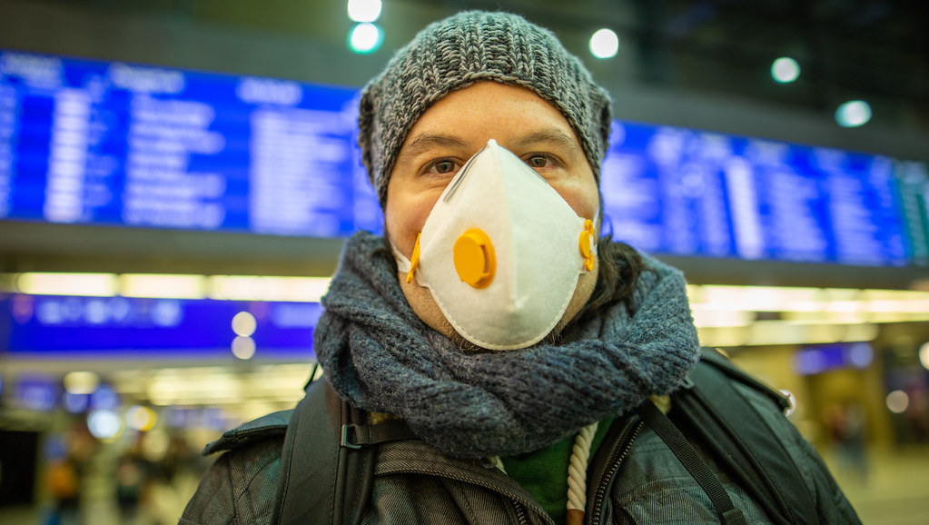 Man in hat and scarf loks at the camera wearing a face mask