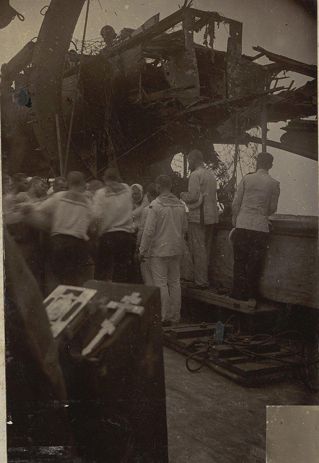 Офицеры, матросы и священнослужитель на палубе повреждённого в бою корабля