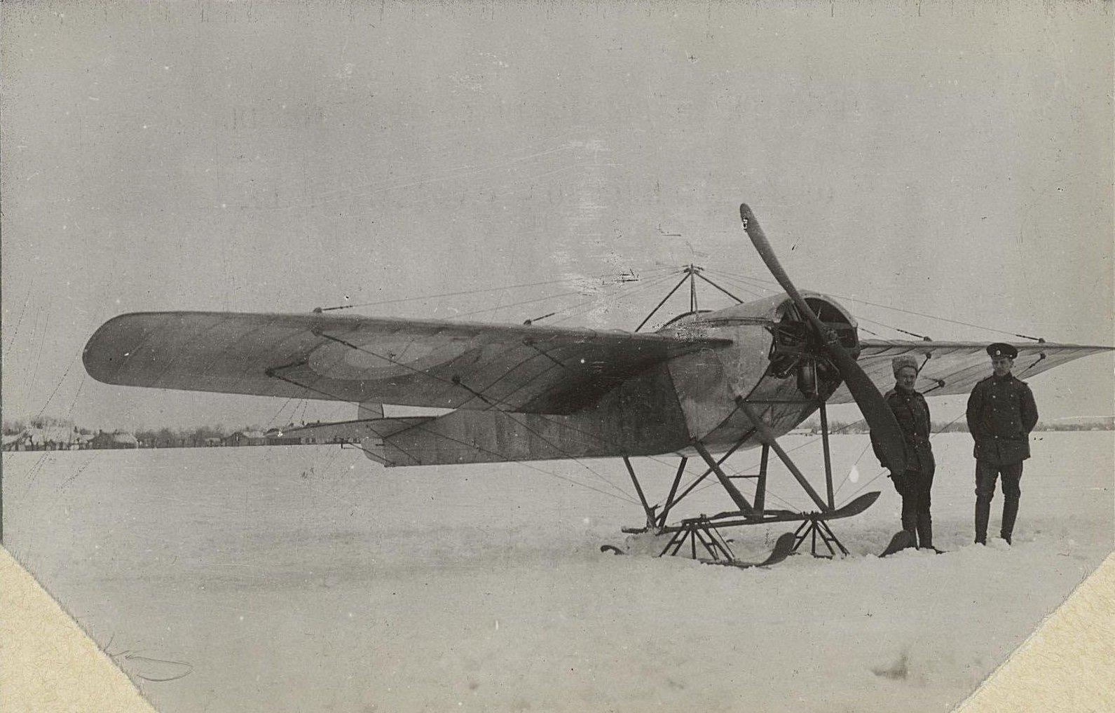 1915. Самолёт на лыжах на снегу. Рядом два лётчика