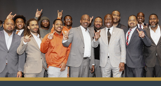 Dr. Moore, Ben Crump, and DDCE staff and students give the Hook 'Em