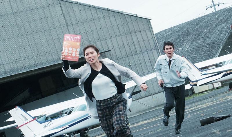 映画『騙し絵の牙』カルチャー誌「トリニティ」を手に飛行場を猛ダッシュする高野(松岡茉優)