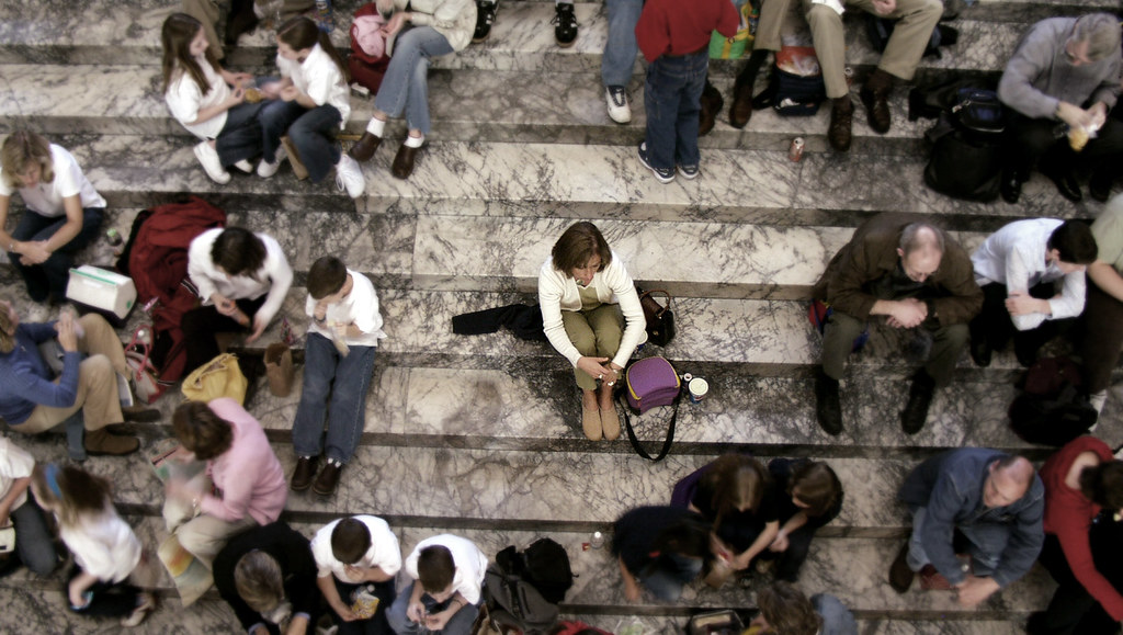 Women sits alone in a crowd