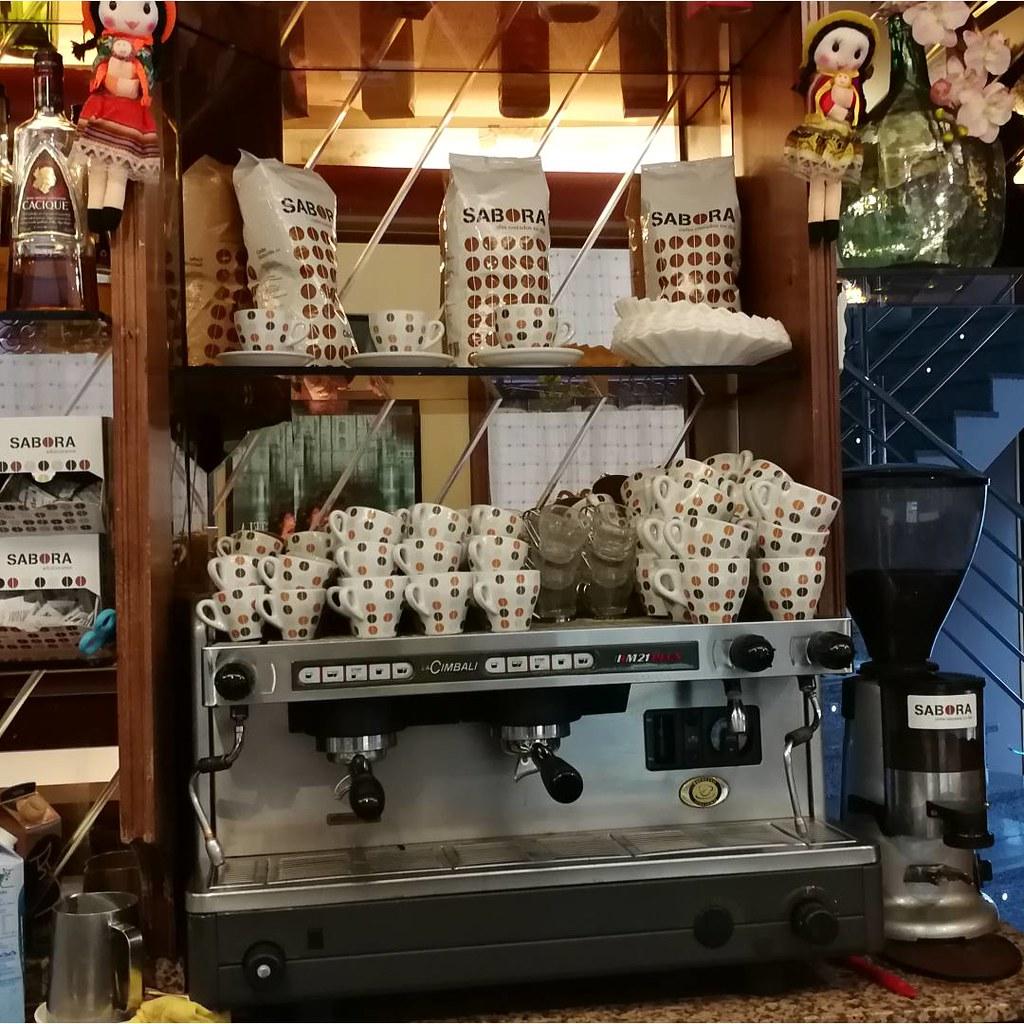 Cafetera expreso en cafetería con tazas en el calienta tazas