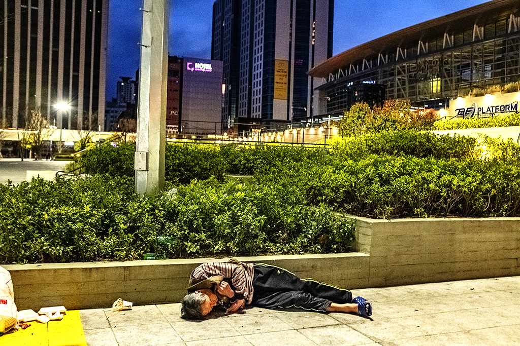 Man sleeping outside train station at 40F on 3-14-20--Busan