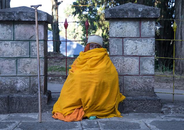Priest covered in an yellow shawl in Entoto orthodox Maryam Church, Addis Ababa Region, Addis Ababa, Ethiopia