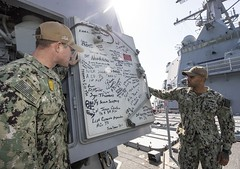 Boatswain's Mate 1st Class Kovadis Maxie II and Master-at-Arms 1st Class Jonathan Cox display the signatures of U.S. Marines who served with Sgt. Rafael Peralta, in a gun mount aboard USS Rafael Peralta (DDG 115). (U.S. Navy/MC2 Jason Isaacs)