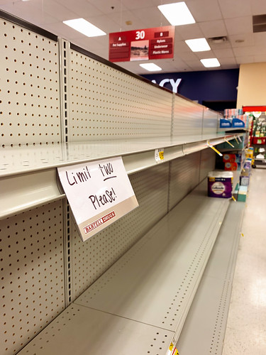 "Everet, WA /USA - 03/14/2020 Empty Shelves with a sign that says ""Limit two Please"" where toilet paper was stocked. Everett WA. is where the first confirmed CoronaVirus patient in the United States was hospitalized. 