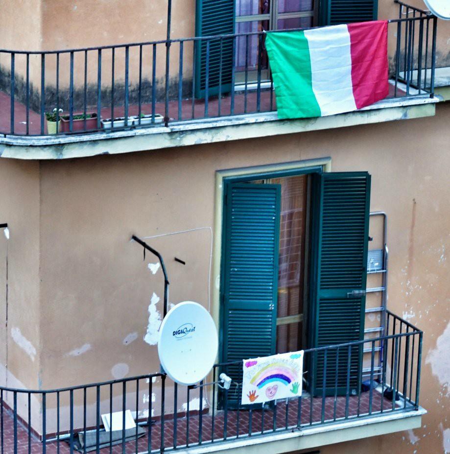 Italialaiset ripustavat nyt parvekkeilleen Italian lippuja ja sateenkaarin koristeltuja piirustuksia, joissa lukee Andra tutto bene!