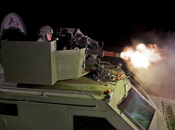 A man atop an armored vehicle fires a machine gun.