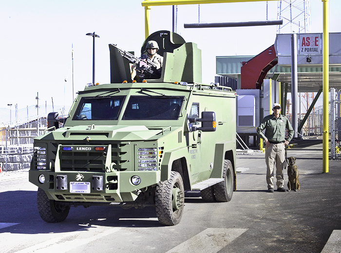 A man atop an armored vehicle. Next to the vehicle stand a man and a dog.